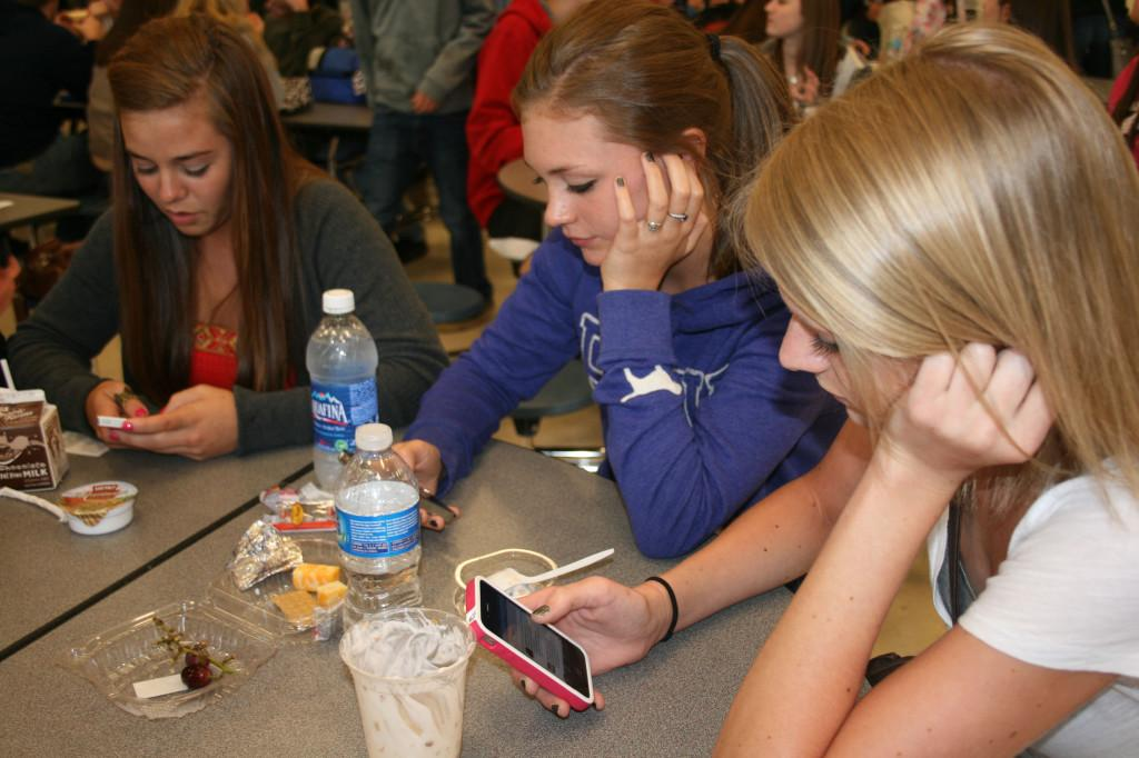 Seniors Sam Hansen, Anna Olson and Kaitlyn Kolzow check their Facebook profiles during lunch.