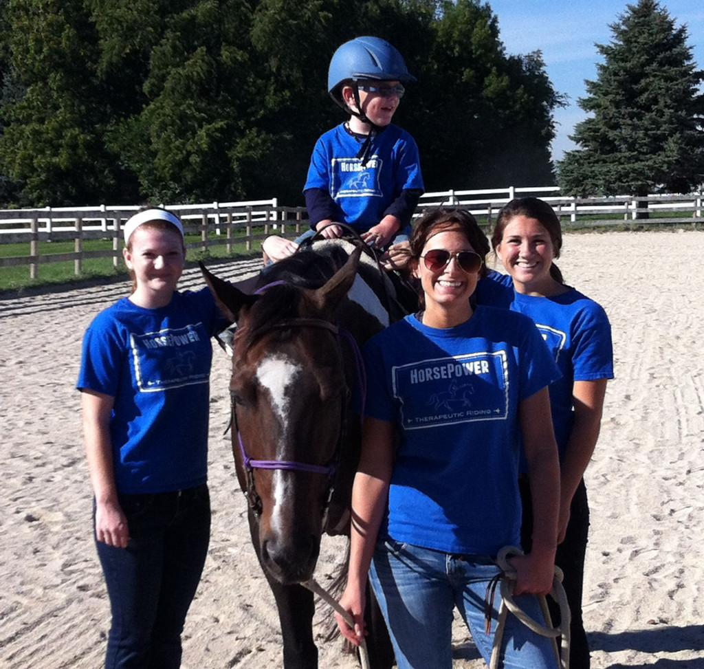 Junior Julia Lennon and seniors Hayley Contorno and Lanie Callaghan volunteer as side walkers at HorsePower Therapeutic Riding