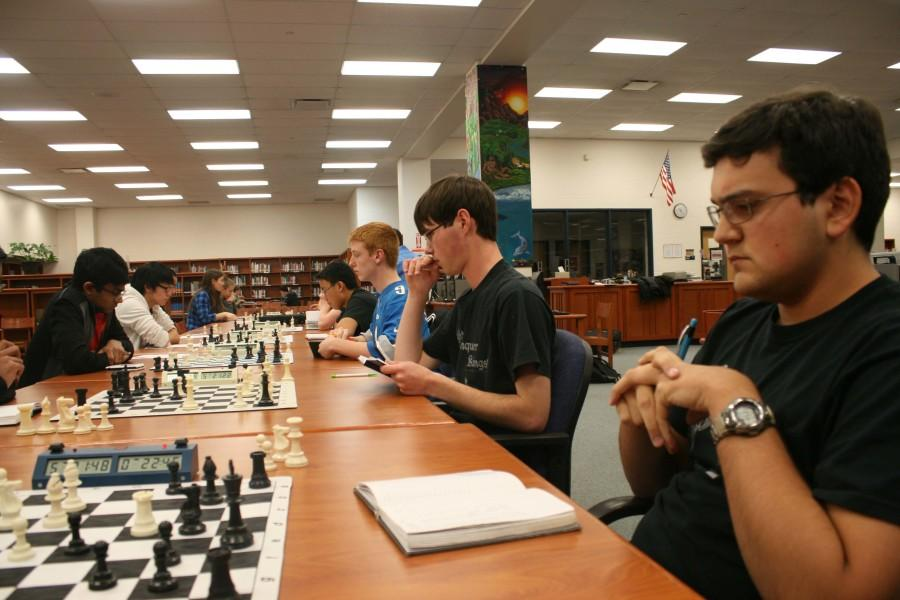The Chess team plays several games at once in the Kaneland High School library during their season.
