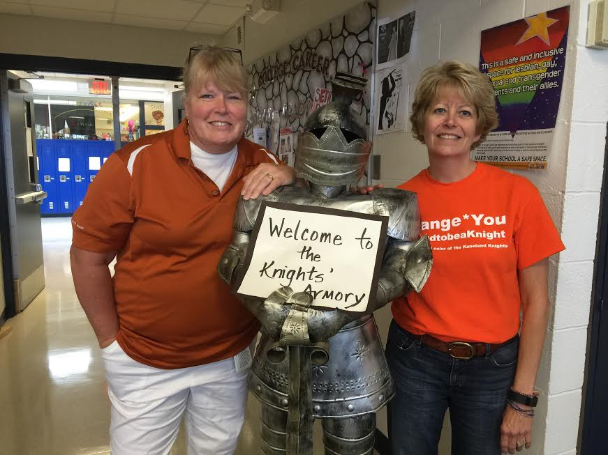 Mrs.+Biddle+and+Mrs.+Komel+welcome+students+to+the+Knights%27+Armory+while+wearing+their+orange+spirit+week+apparel.+