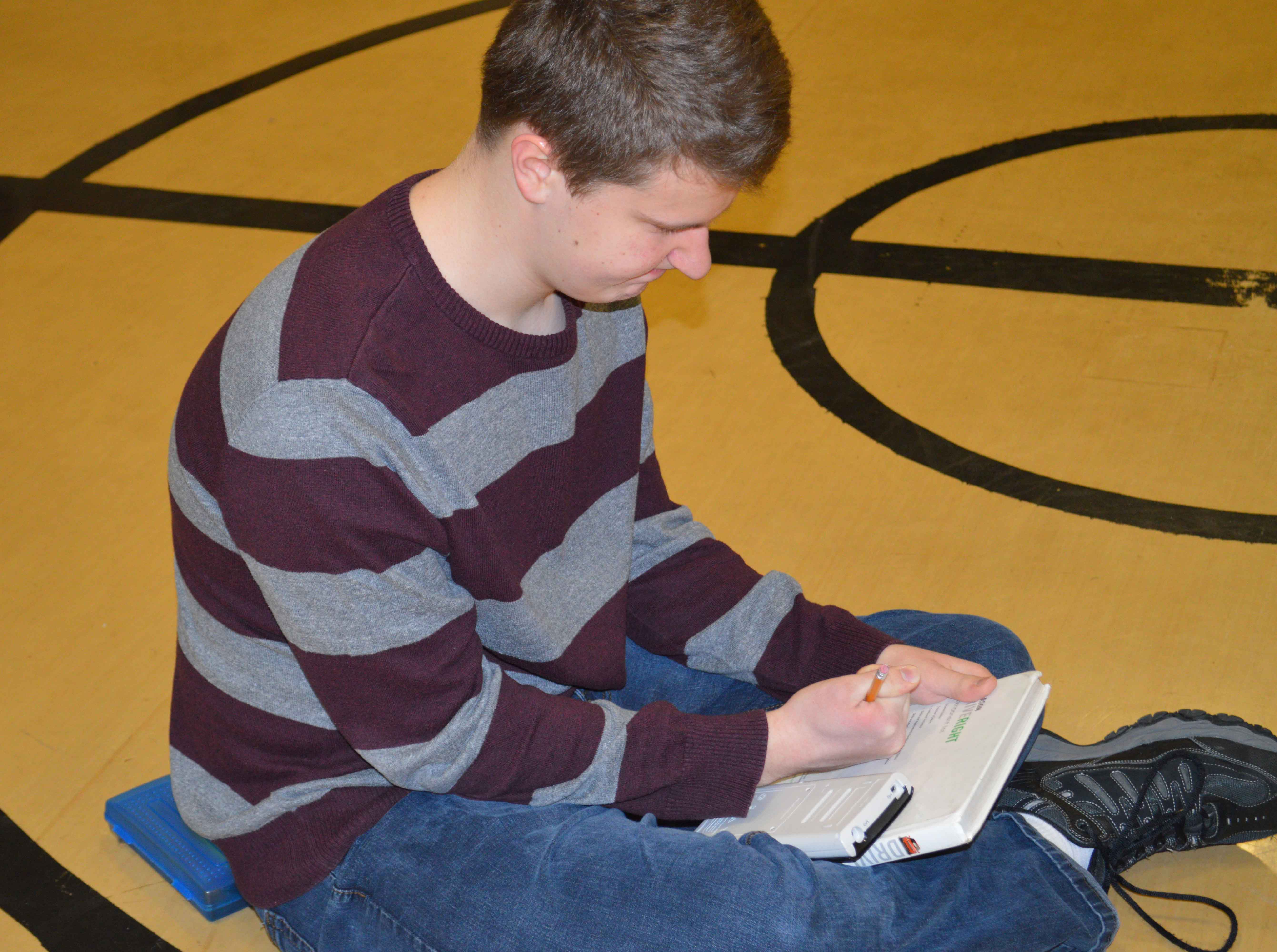 Students rush to do their homework while fulfilling physical education requirements.