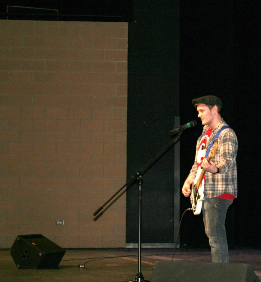 """Junior Stephen Gannon performs a smashing  hit on his bass while singing Cage and the  Elephants' """"Back Against the Wall."""""""