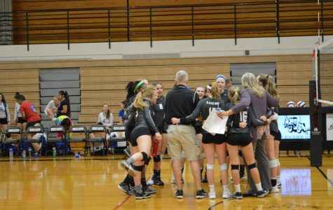 The volleyball team celebrates their regional victory at the end of the game.