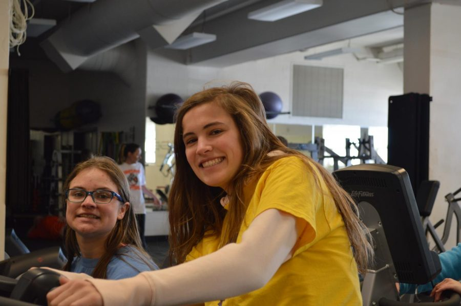 "All smiles from Ashley Hughes and Natalie Kraemer while they pedal away on the bikes talking about their day. ""I always push to go on the bikes because I enjoy working out but also being able to talk with Ashley and how she is doing."" Kraemer said."