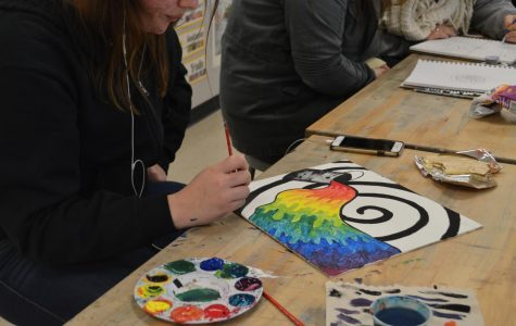 With her paint palette full of all different colors, sophomore Hannah McCarren finishes up her beautiful painting as she comfortably listens to music and has a snack.