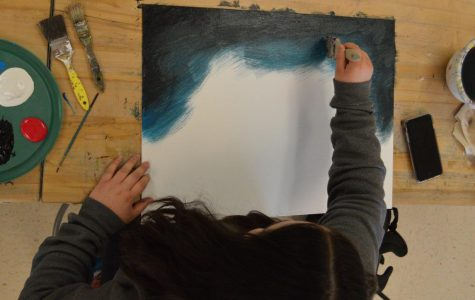 Using a dark blue Alaniz mixes it with the black to give a gradient effect. She continued to bring it down the canvas halfway.