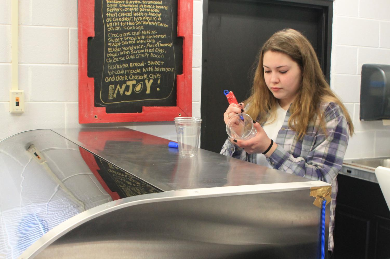 Erin Zollers is writing a drink order on a cup in Cafe 302.