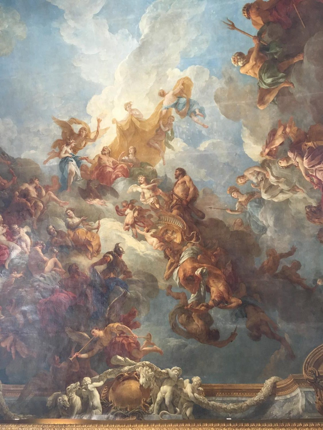 A+mural+covers+one+of+the+ceilings+in+the+Palace+of+Versailles+which+depicts+the+Greek+gods+and+other+mythical+figures.%0A