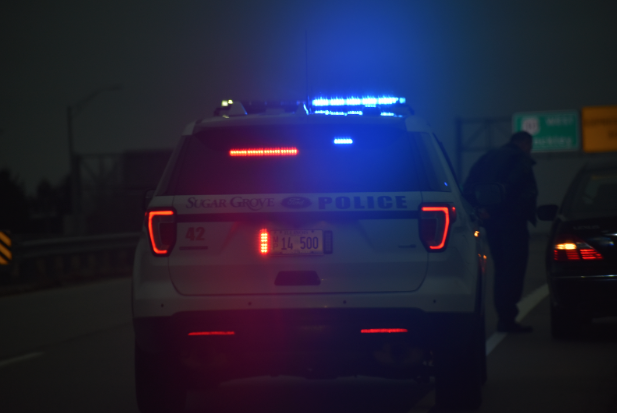 Sergeant Fenili backs up Officer Fred Tichener while he makes a traffic stop. When nearby, officers are required to watch and back up other officers during a stop.
