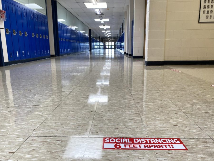 Social+distancing+signs+have+been+placed+throughout+Kaneland+High+School+in+advance+of+students%27+first+in-person+day+of+Thursday%2C+August+20.+A+typically+crowded+hallway+stands+empty+now%2C+but+will+look+different+next+week.