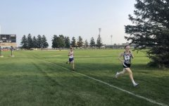 Senior Aaron Lodwig runs through the finish at the Kaneland vs. Marmion vs. Sandwich boys varsity cross country meet.
