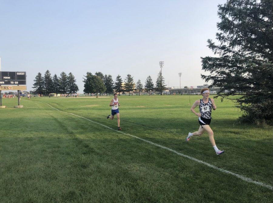 Senior Aaron Lodwig runs through the finish at the Kaneland vs. Marmion vs. Sandwich boys varsity cross country meet.
