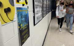 Students during a passing period walk by the new Homecoming poster, which announces the Starry Night theme. The poster was designed by sophomore Jessica Wrobel, who is a part of the Homecoming Committee.