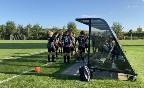 The varsity soccer players gather during halftime to prepare for the second half. The players like to converse to get on the same page before going back out on the field.